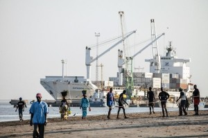 Banjul,_Gambia_Local_people_at_the_city_beach,_commercial_port_with_a_big_container_ship_in_background._592_394_84_c1